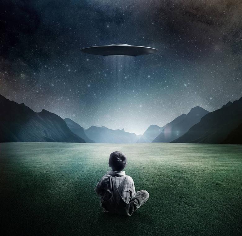 Мальчик сидит на зеленой траве и смотрит на зависшую в воздухе летающую тарелку