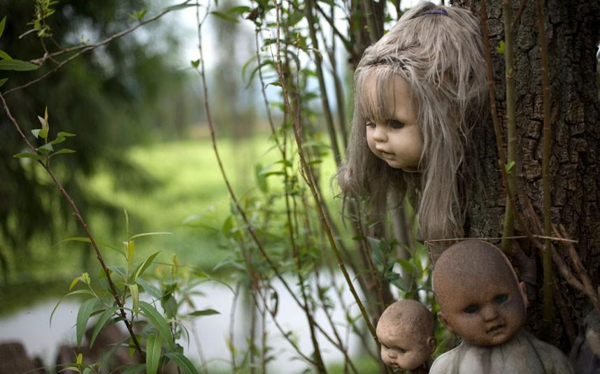 Куклы развешаны на деревьях