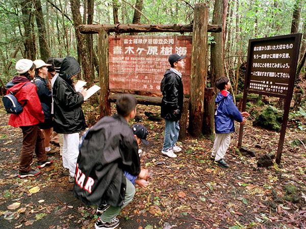 Экскурсия школьников читает предупреждения для самоубийц.