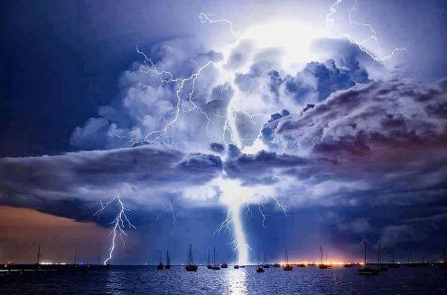Корабли, плывущие по воде, освещены вспышками молний